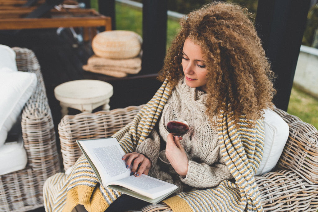 woman who can't sleep is reading and drinking glass of wine