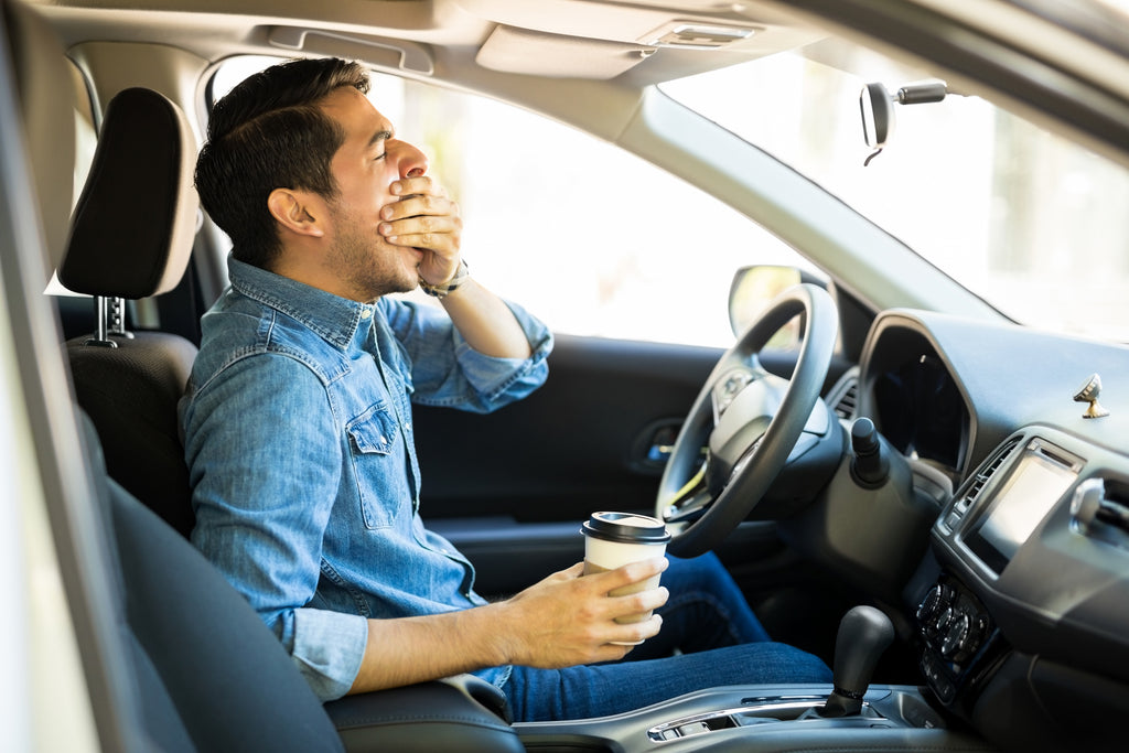 drowsy driver yawns at the wheel holding coffee after skimping on sleep