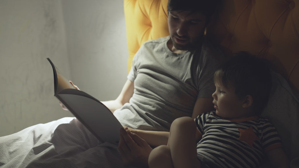 Father reading bedtime story to son which is the language of sleep