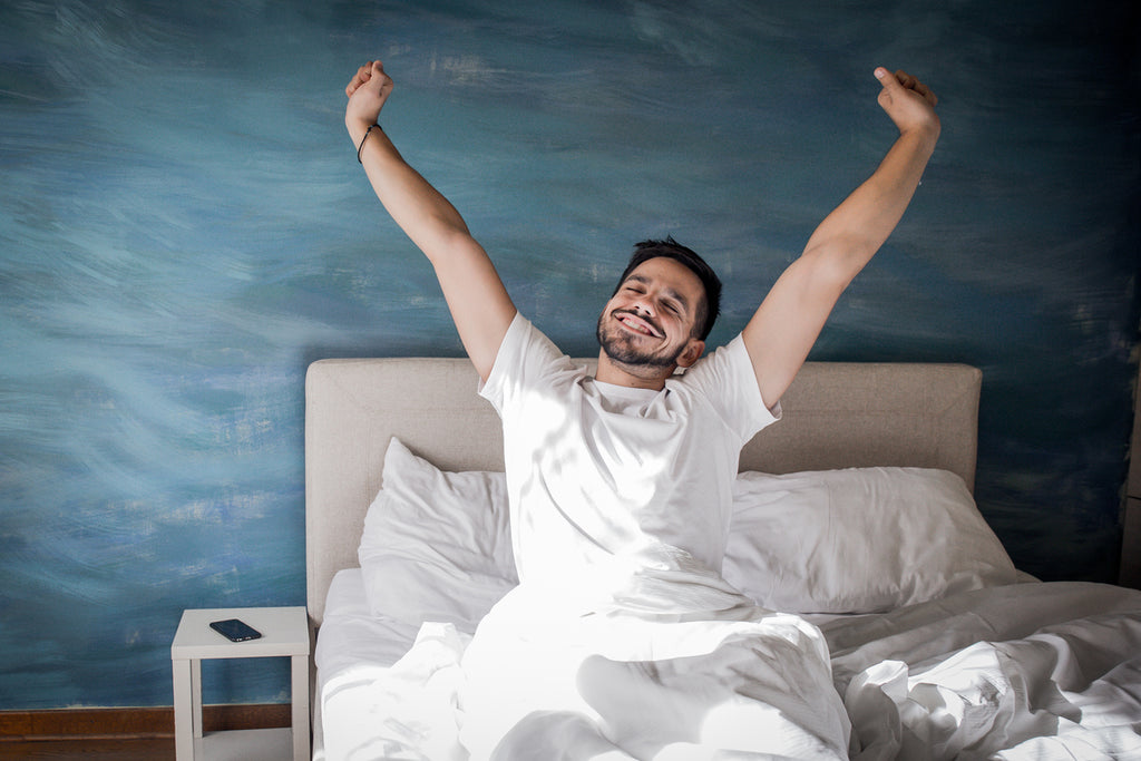 happy man stretching in bed in the morning