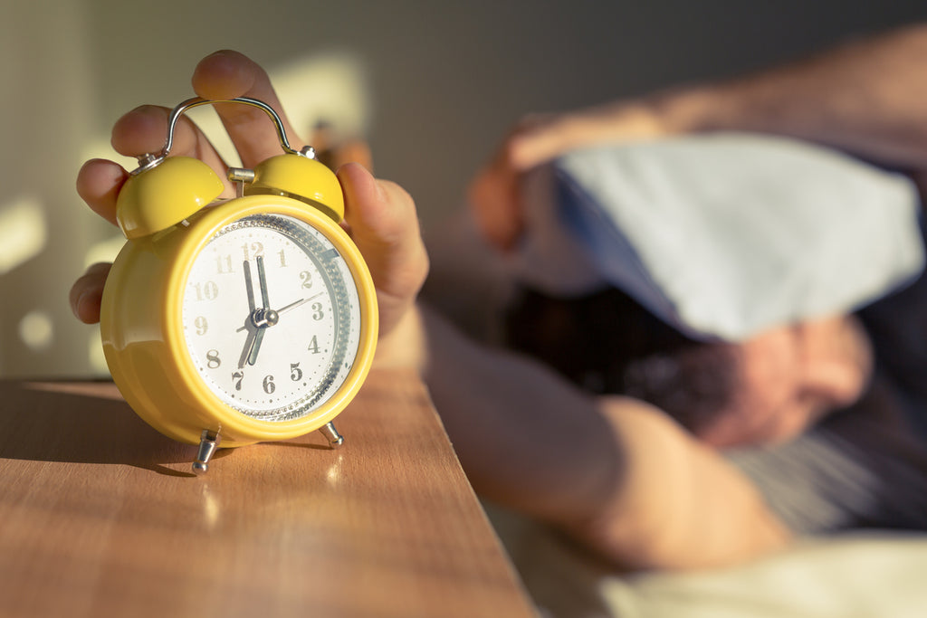 Man in bed trying to wake up on time without hitting snooze