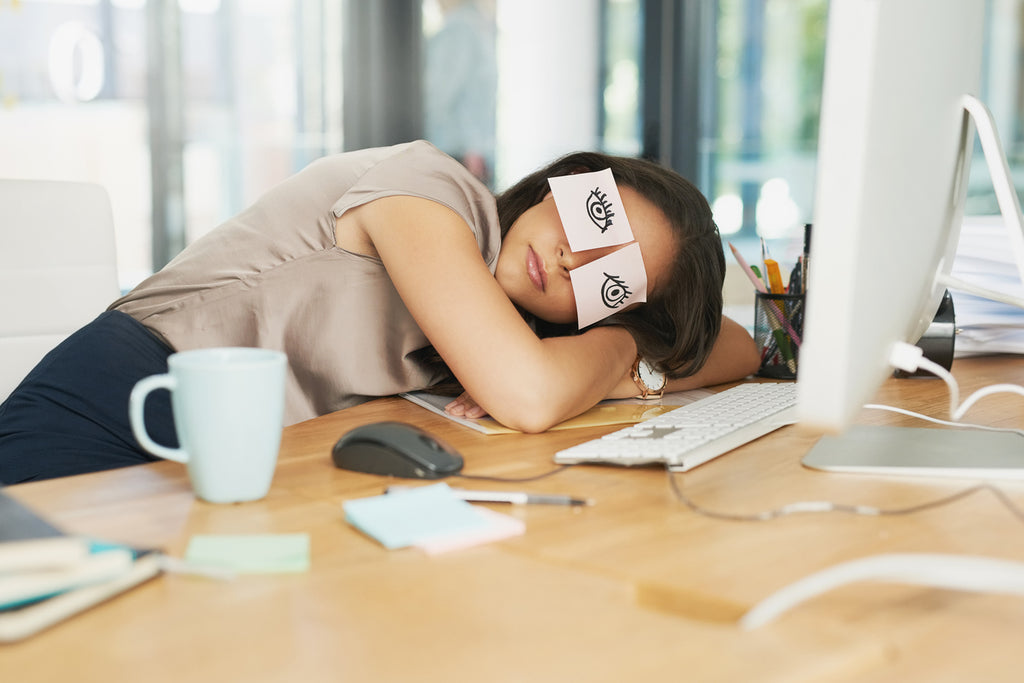 Businesswoman sleeping at desk after trying to stay awake at work without caffeine