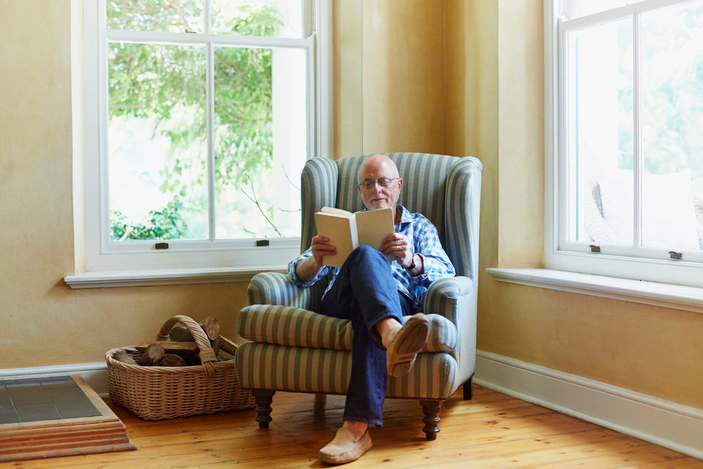 man reading a book in a corner lounge chair