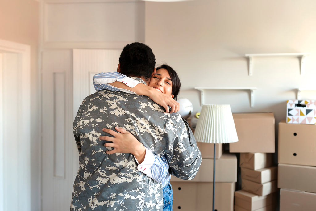 military moving day partners hug surrounded by cardboard boxes