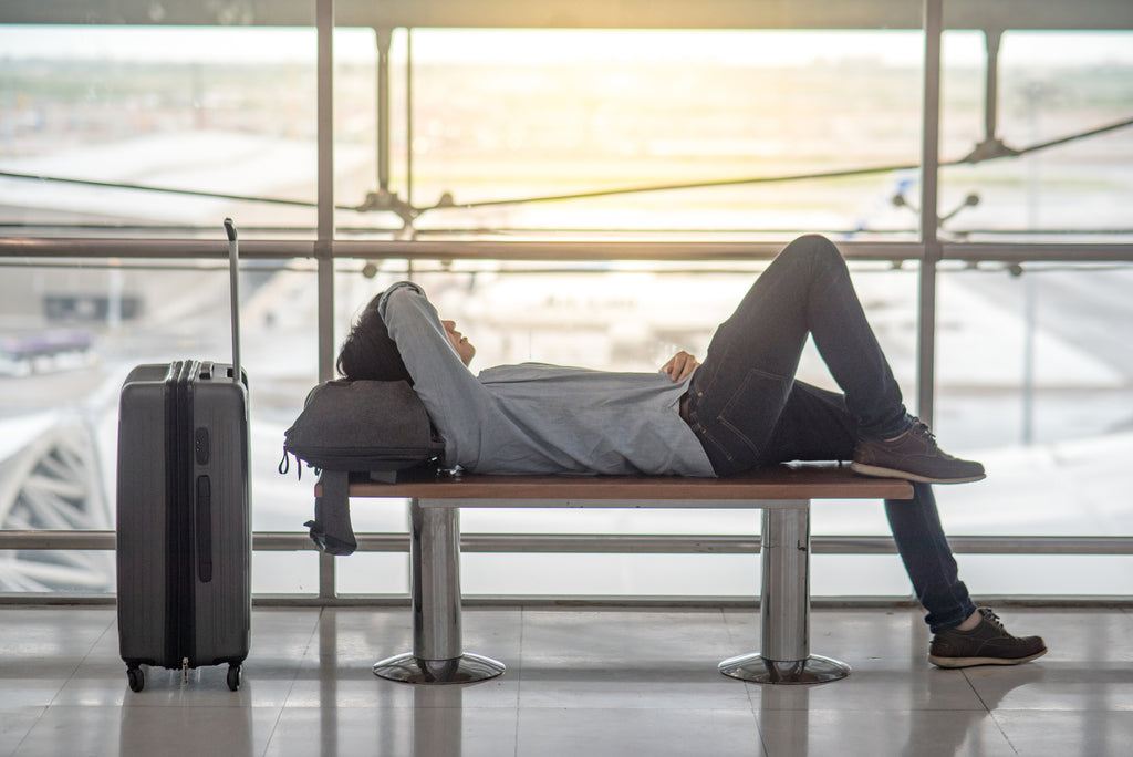 person sleeping in an airport on a bench