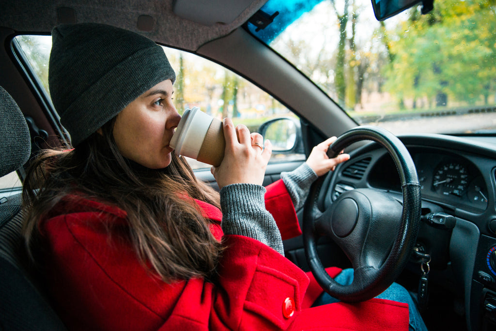 woman driving on a road trip and sipping coffee in autumn coat