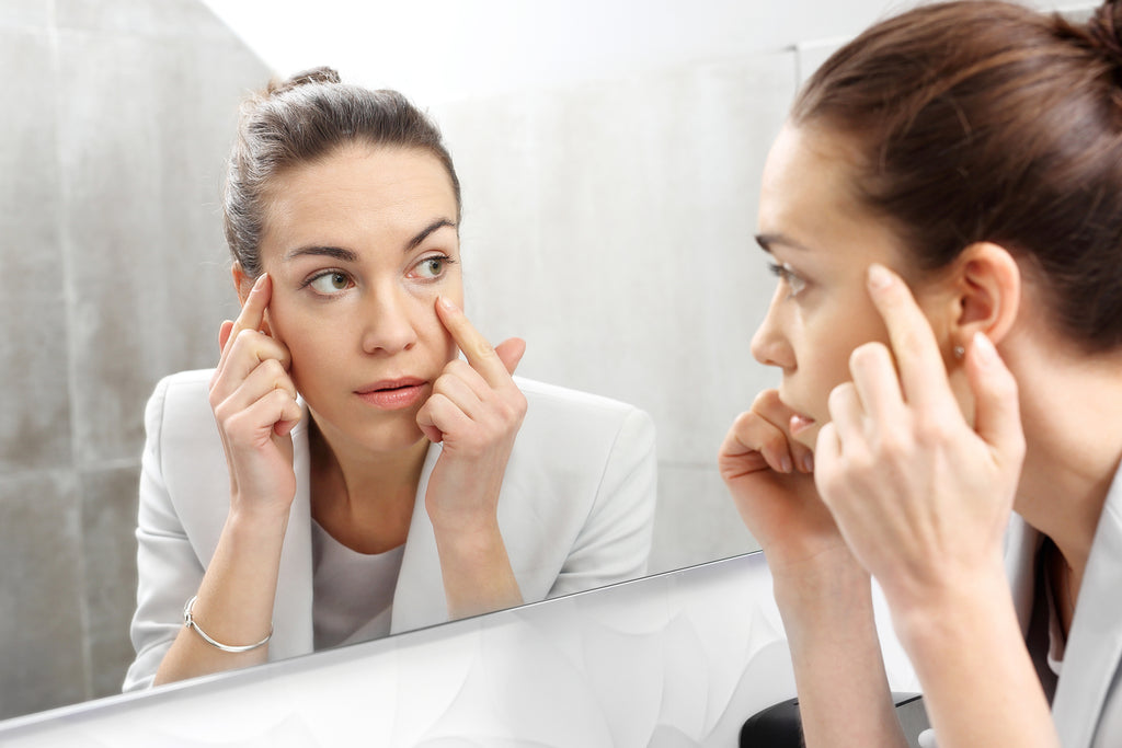 woman looking at eye wrinkles in mirror