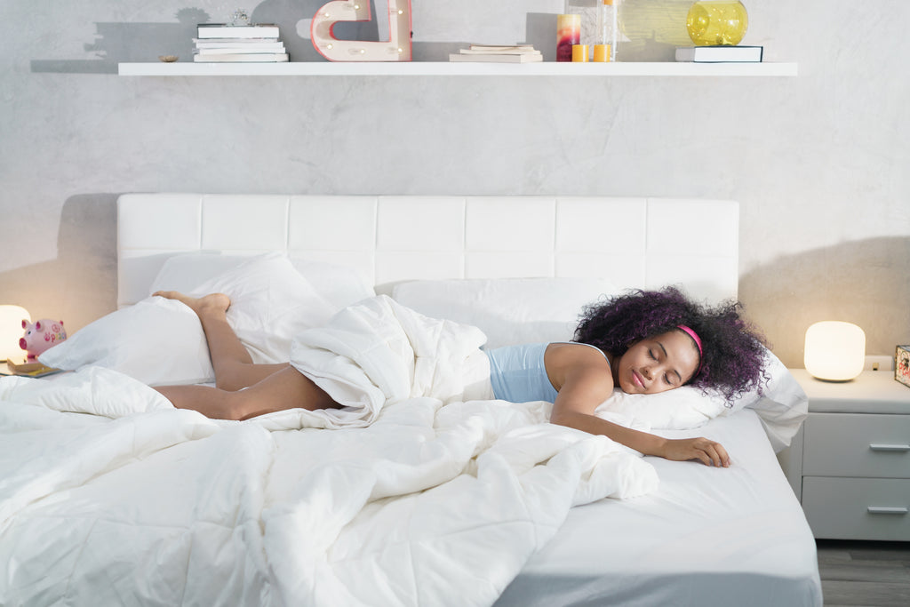 woman lounging across bed with extra set of sheets