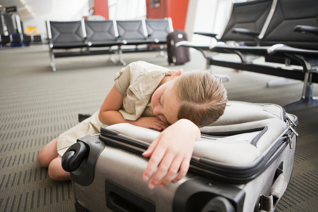 woman sleeping on suitcase in airport