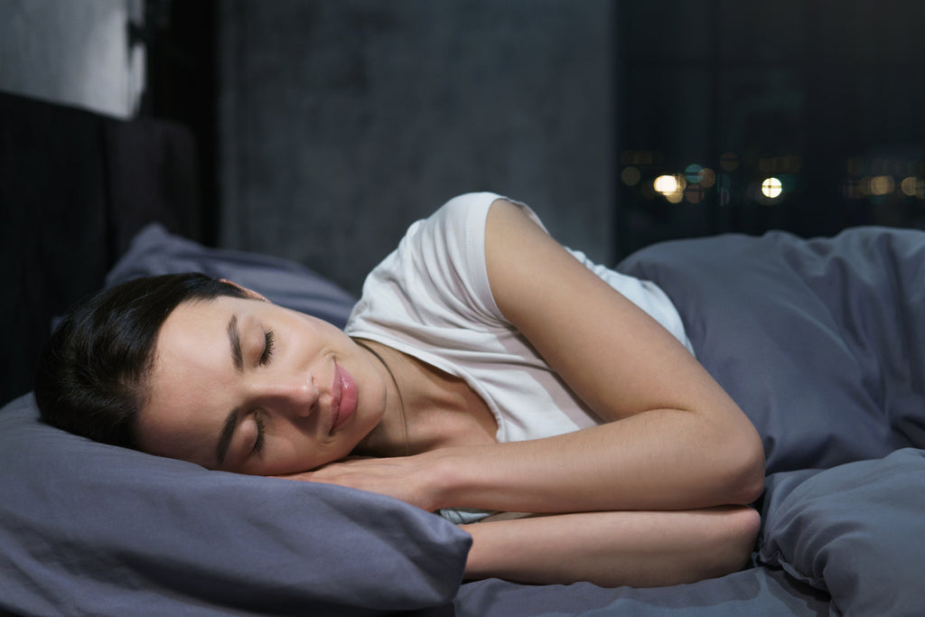 woman sleeping soundly in dark bedroom sleep chamber