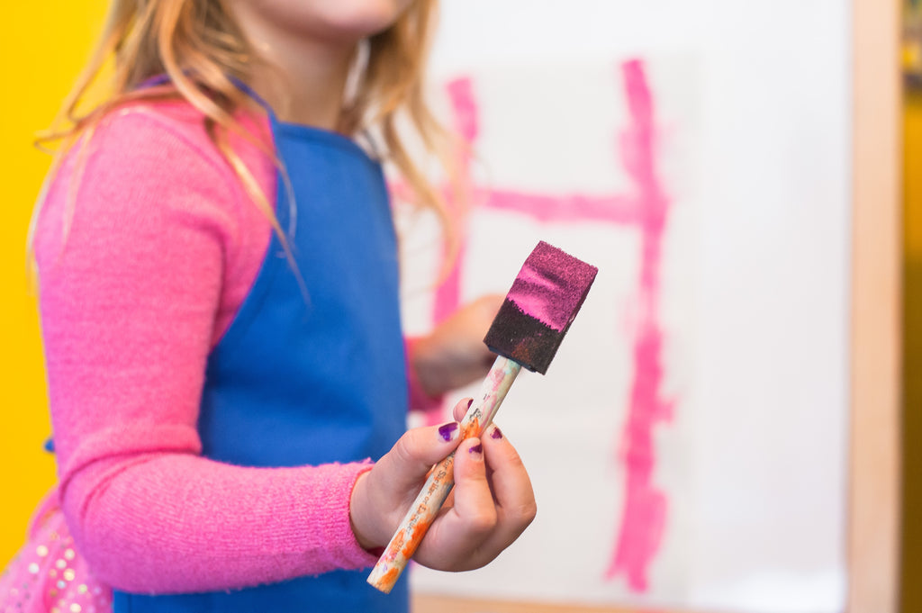 young girl painting with sponge brush