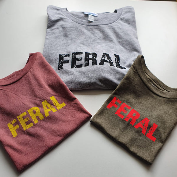3 kids unisex ts with the FERAL slogan. Clockwise grey t with black ink, olive t with glow coral ink and a mauve t with yellow ink.