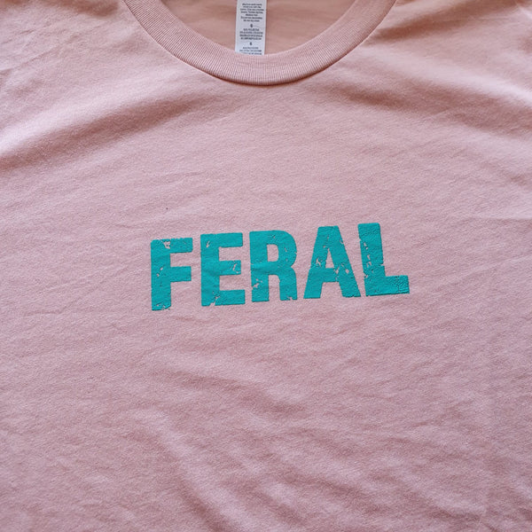 Peach kids unisex t with the FERAL slogan in green ink.