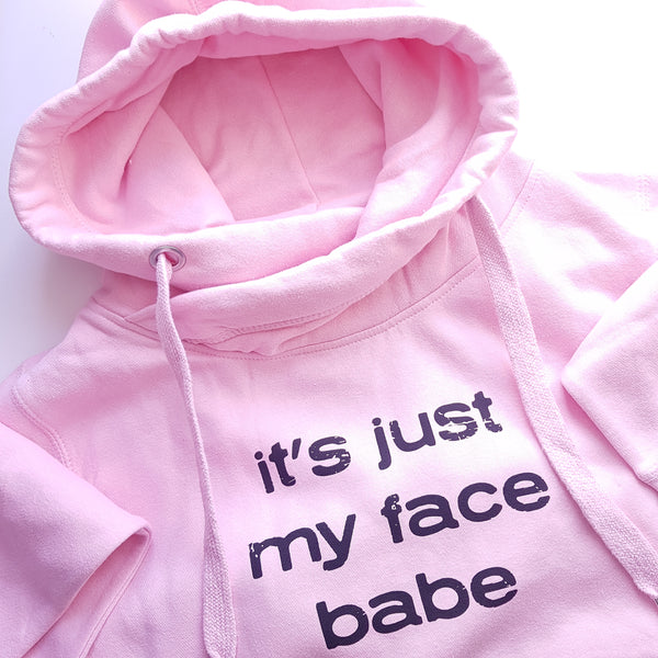 Baby pink cowl neck hoody with the it's just my face babe slogan in black ink.
