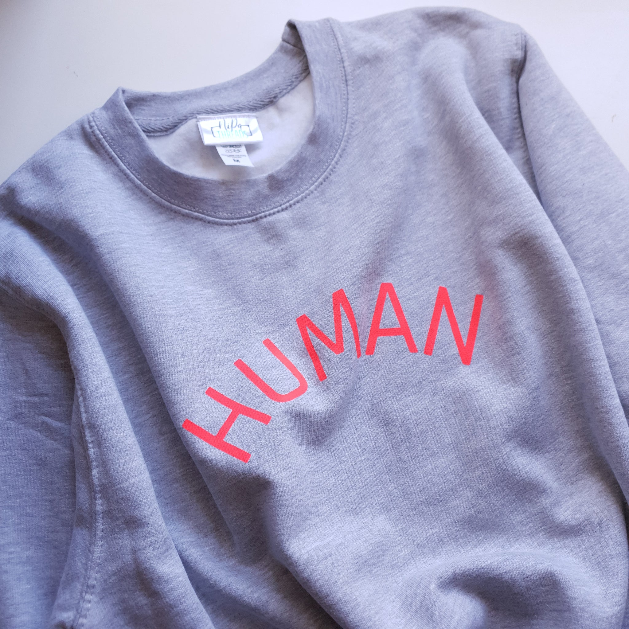 Light grey adult unisex sweatshirt with the HUMAN logo in glow coral ink.