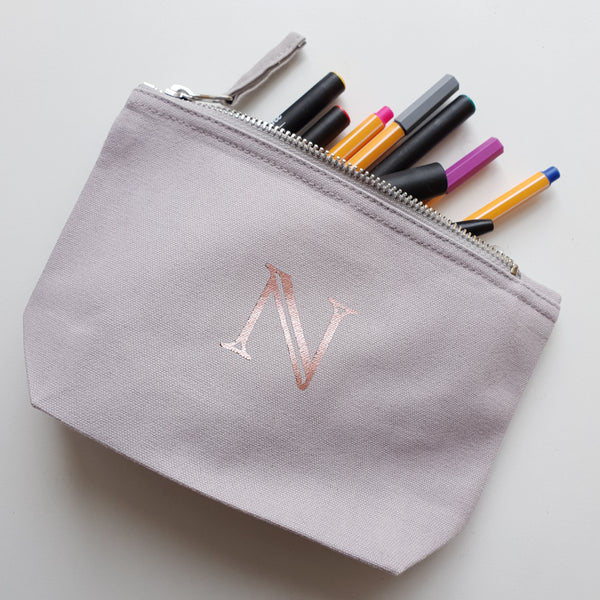 Grey initial pouch with N in rose gold foil. Pens coming outvote top.