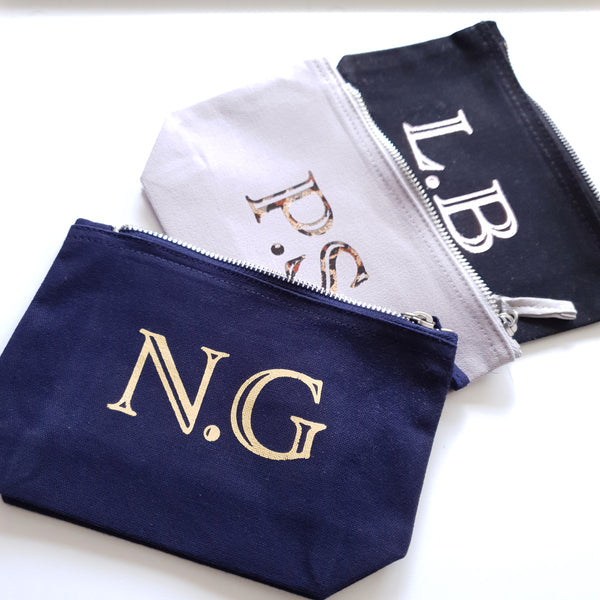 3 initial pouches. From the top black with L.B in rose gold foil, grey pouch with P.S in leopard print foil and navy blue pouch with N.G in gold foil.