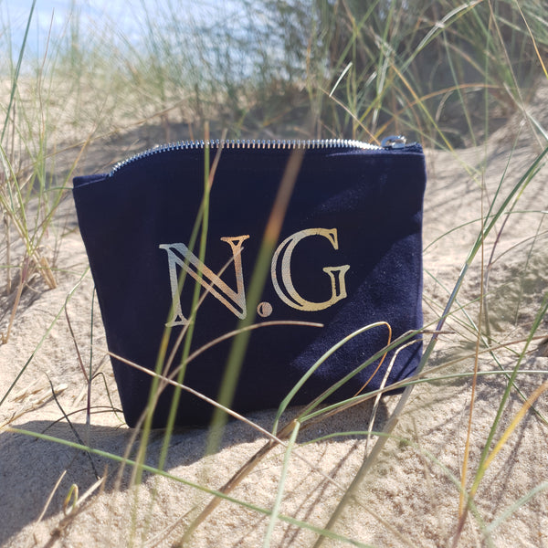 Navy blue initial pouch with N.G in gold foil.