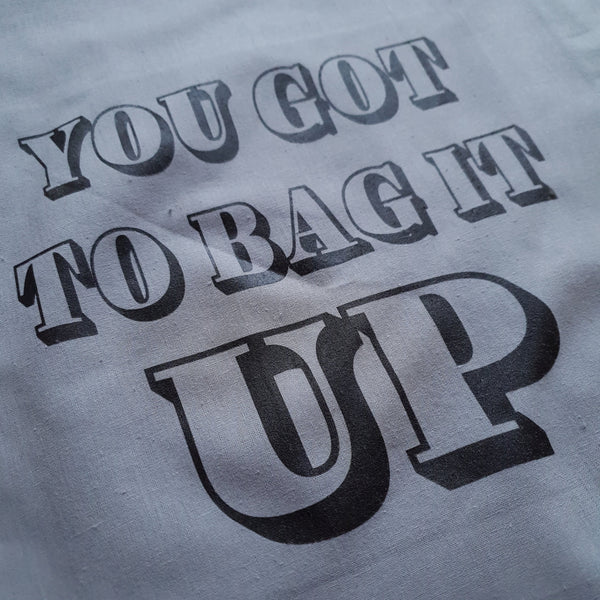 grey tote bag with black print you got to bag it up slogan