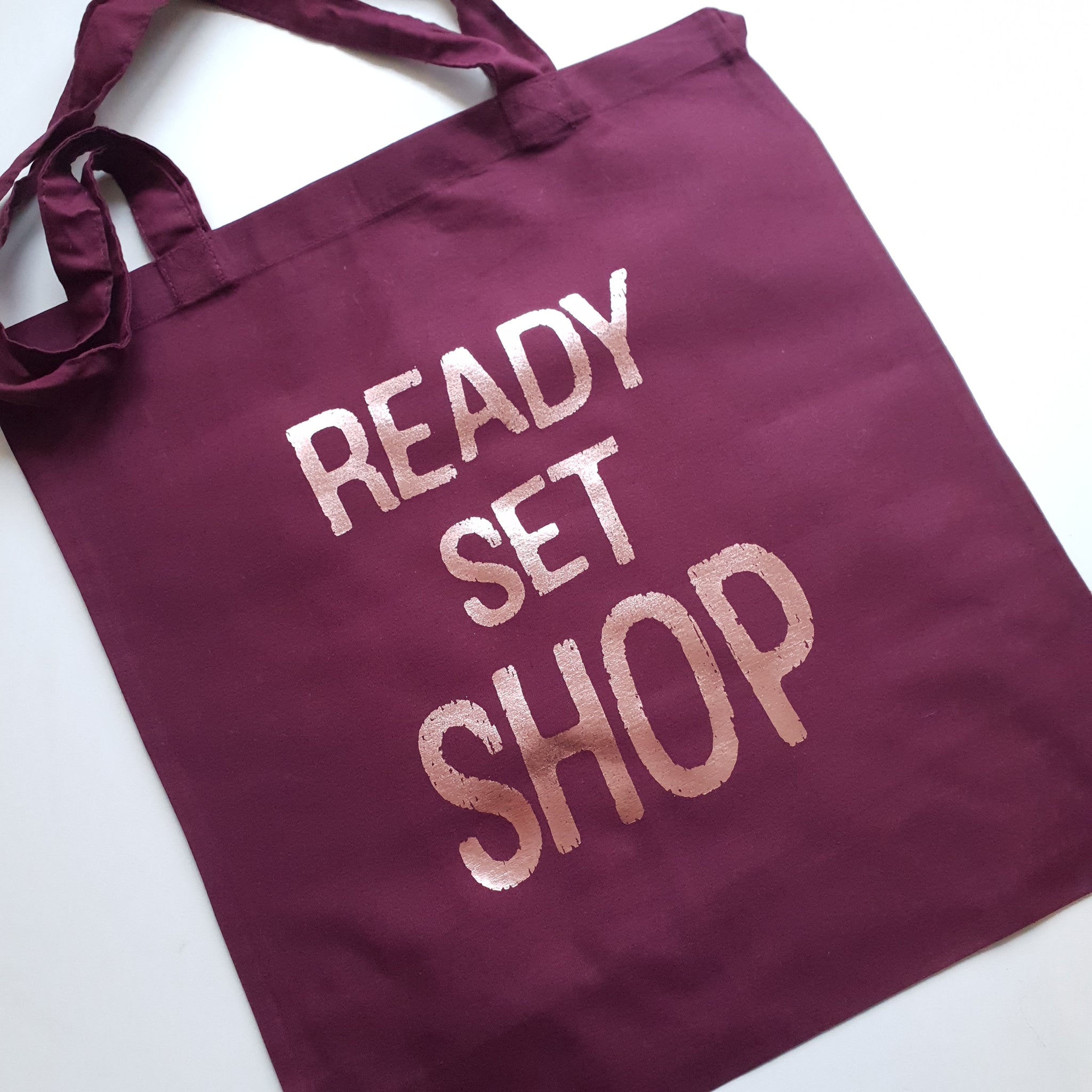 Burgundy tote bag with rose gold ready set shop slogan