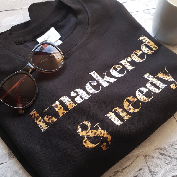 Black unisex sweatshirt with leopard print knackered and needy slogan