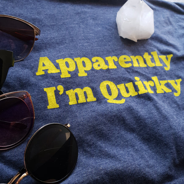 Navy blue adults unisex t with the apparently im quirky slogan in yellow ink.