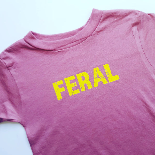 Mauve kids unisex t with the FERAL slogan in yellow ink.