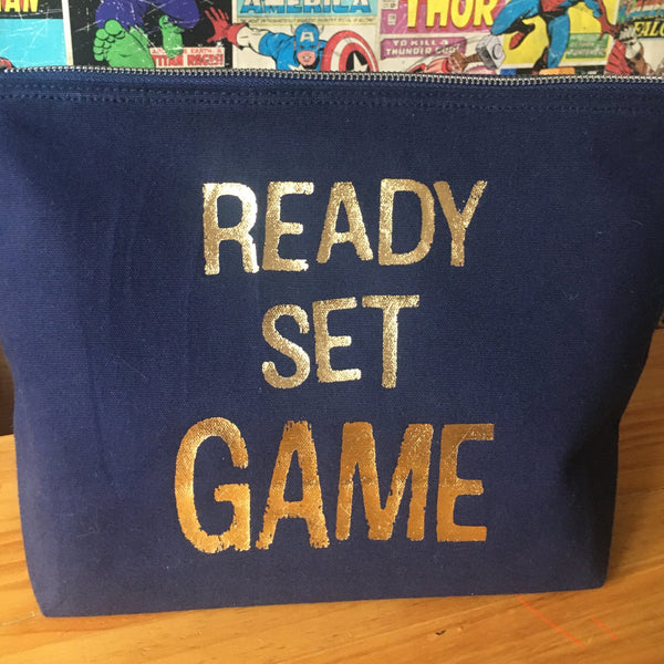 Large navy blue pouch with the ready set game slogan in gold foil.