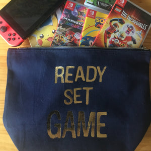 Navy blue large pouch with the ready set game slogan in gold foil. Games coming out of the pouch.