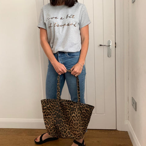 Grey adult unisex t with the love a bit of leopard slogan in leopard print foil. Teamed with blue denim jeans black sandals and a leopard print tote bag.