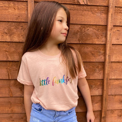Peach kids unisex t with the little funkster slogan in rainbow foil.