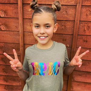 Girl wearing olive kids tee with rainbow print epic slogan