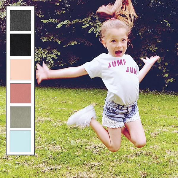 Ice blue kids unisex tee with the jump jump slogan I glow pink ink. paired with denim shorts the model is jumping.