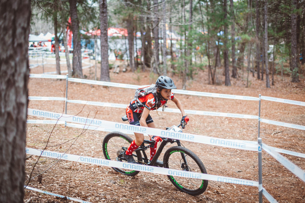 NICA mountain bike racer on course.