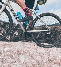 Load image into Gallery viewer, Riding over rock in the Purpel cycling sock