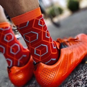 Cyclist wearing Beehive socks with matching orange cycling shoes.
