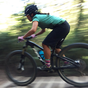 Woman mountain biker in the forest wearing The Dreamer socks from Mint.