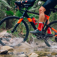 Load image into Gallery viewer, Rider splashes through a creek wearing the Red Racer sock