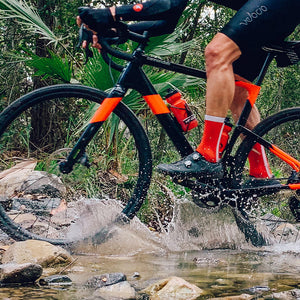 Rider splashes through a creek wearing the Red Racer sock