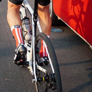 Cyclists rides past a red van with Red Racer socks