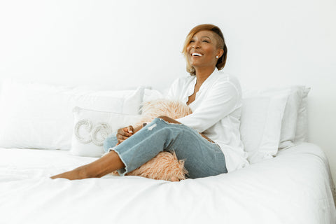 Kalisha Price sitting at home in bed with a sense of peace and happiness on her face