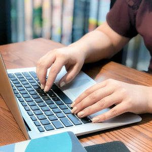 close up image of hands typing on an Apple MacBook Air laptop