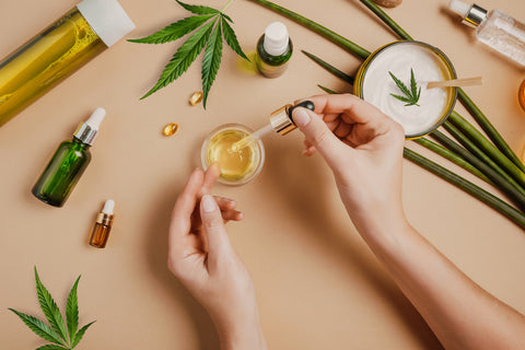 close-up photo of a woman's hands as she mixes cbd oil into various products and creams