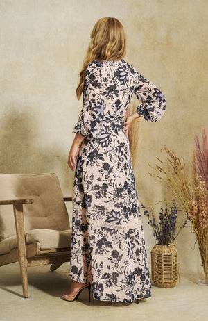 Hope & Ivy Wrap Front Maxi Dress With Gather Sleeve And Contrast Lace Trim in a hand designed print. Stylized blooms bedeck the soft pink background, in beautiful blue hues. The classic wrap shape is elevated by contrast lace trims, finished off with full statement sleeves and tie waist detailing.