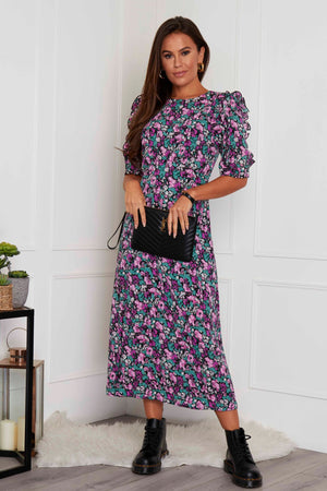 This is our brand new midi dress in beautiful purple floral print . Featuring frill sleeve detailing side skirt slit . Be talk of the town in this stunning dress . Dress it up with heals or down with trainers..