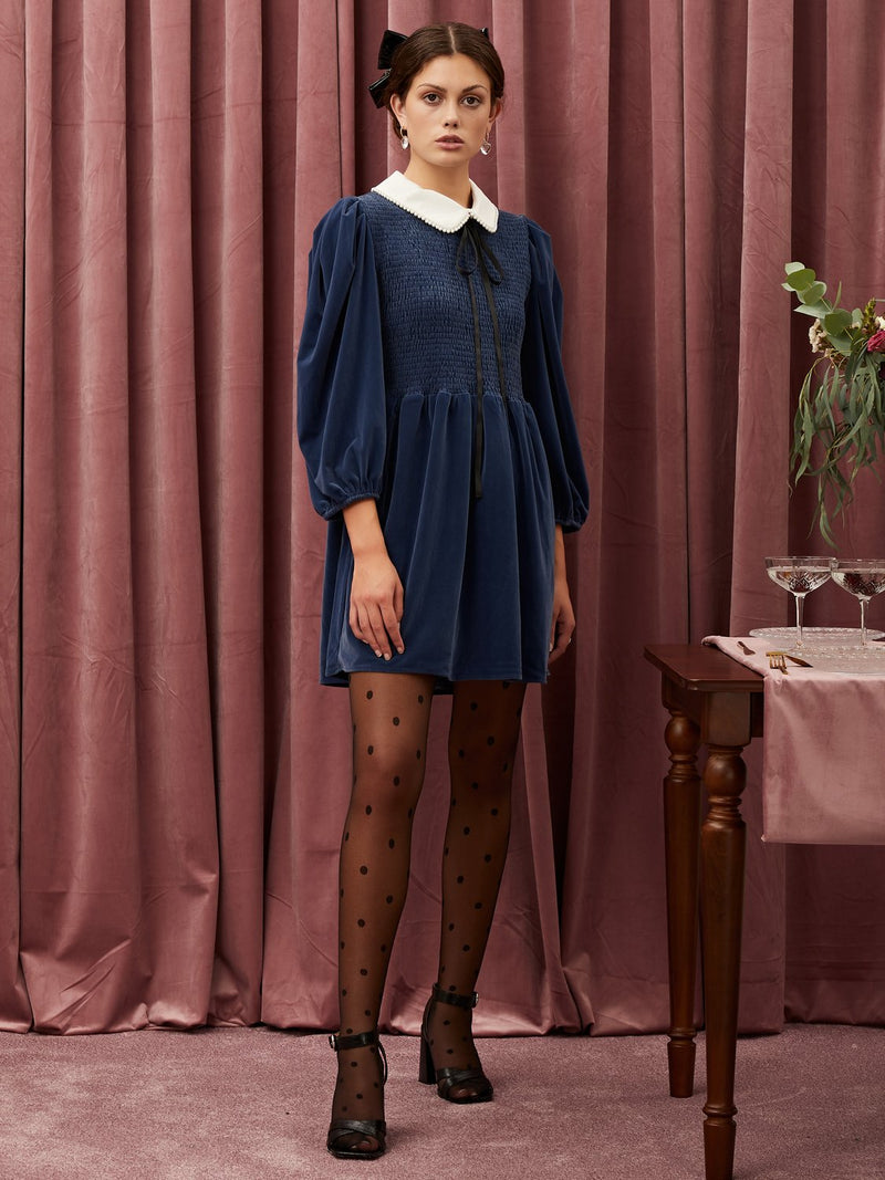 Sister Jane Mini dress in a soft velvet fabric. Featuring a smocked bodice and puff sleeves. The collar is detailed with a pearl trim and an extra long neck tie fastens at the front. This style is unlined.