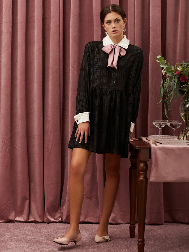 Oversized mini dress in a sheer textured fabric. Featuring a contrast collar with pearl detail. A removeable bow finishes the look.