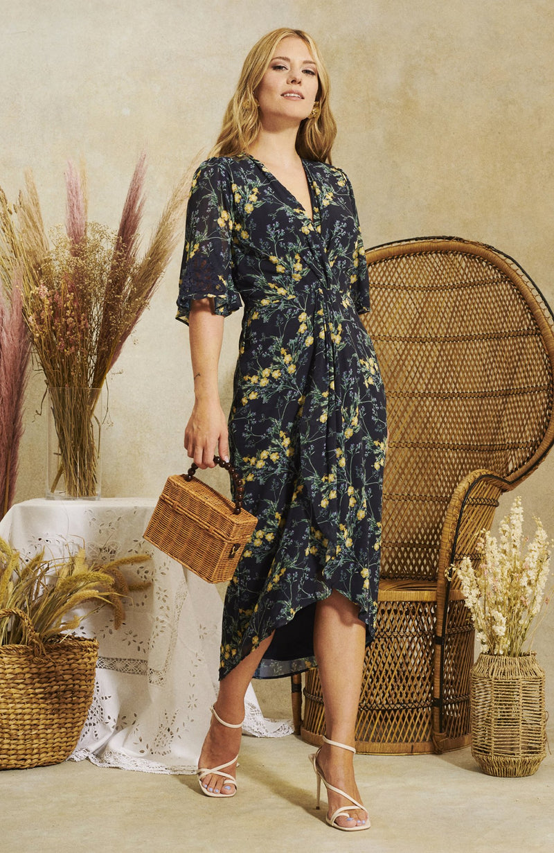 Hope & Ivy The Daisy Kimono Front Midi Dress With Contrast Lace Back in hand designed print. Exude flair and fabulousness in this classic creation. Delicate hand-designed florals brush the warm navy base, budding blooms in bright yellows and greens. With an open kimono sleeve and knot front wrap skirt, this shape skimming style flatters every form.