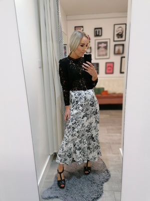 High waist white midi skirt with black floral print and ruffle hem.