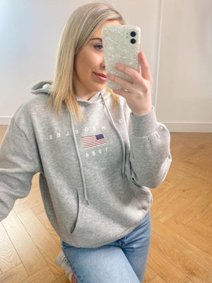 This hoodie features a print on the front with white writing, perfectly contrasting with the grey background. Perfect for a casual look.  Drawstring Hoodie Pocket Fleece Lined Measurements: Approx Overall Length 62 cm Care Instructions: Machine Washable Material: 80% Cotton 20% Polyester